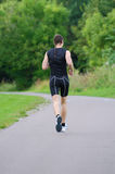 Sportsman running. In park. Back view Royalty Free Stock Image