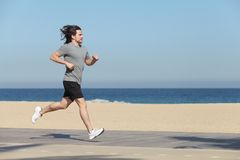 Sportsman running on the seafront of the beach Stock Images