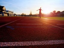 Sportsman on running stadium racetrack. Adult in evening training Royalty Free Stock Photos