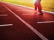 Sportsman on running stadium racetrack. Adult in evening training Royalty Free Stock Images