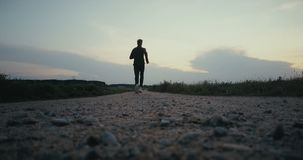 Sportsman running towards rural sunset panorama. Freedom. Back view on quiet autumn road. Cinematic ending steady shot. Sportsman running towards rural sunset stock footage