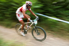Sportsman's on white bike motion photo Royalty Free Stock Image