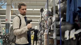 Sportsman is selecting a dumbbell for him in a shop, trying weight stock footage