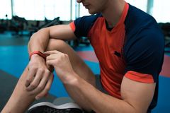 Sportsman Setting Mode of Activity Tracker. Mid-section portrait of unrecognizable modern sportsman checking fitness activity tracker sitting on floor in gym stock photo