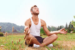 Sportsman sitting on grass Royalty Free Stock Photo