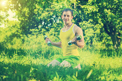 Sportsman sitting on grass and lifting weights in park field ins Royalty Free Stock Images