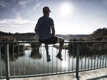 Sportsman is sitting on handrail in the park. Feet of jogging man stock photo