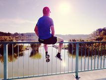 Sportsman is sitting on handrail in the park. Feet of jogging man royalty free stock images