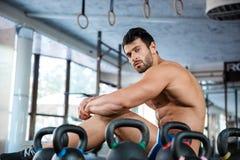 Sportsman sitting near kettle balls stock photo