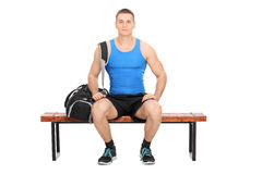 Sportsman sitting on a wooden bench Royalty Free Stock Image