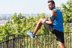Sportsman stretching in park. Sportsman with smartphone in arm band stretching in park Stock Image
