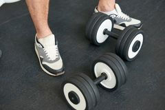 Sportsman in sneakers standing with dumbbells on the floor. royalty free stock photography