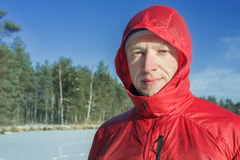 Sportsman in snowy winter outdoor landscape wearing red protective nylon jacket Royalty Free Stock Image