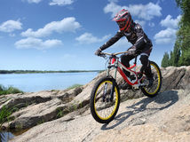 Sportsman in sportswear on a mountain bike rides on the stones Royalty Free Stock Photography