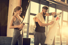 Sportsman and sportswoman make a plan on white board in sports center stock photo