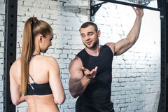 Sportsman and sportswoman talking and looking at each other in gym Stock Photos