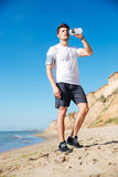 Sportsman standing and drinking water on the beach Royalty Free Stock Photo