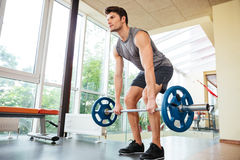 Sportsman standing and lifting barbell in gym Stock Photos