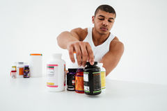 Sportsman standing over white background holding vitamins Stock Images