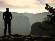 Sportsman is standing on the peak of sandstone rock in rock empires park and watching over the misty and foggy morning valley Royalty Free Stock Photography