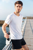 Sportsman standing on pier and holding bottle of water. Portrait of attractive young sportsman standing on pier and holding bottle of water Royalty Free Stock Image