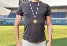 Sportsman is standing in stadium and wearing golden medal Royalty Free Stock Photography