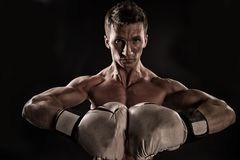 Sportsman with stern look on black background. Man with muscular body wearing boxing gloves. Athlete at. Training, strength and self discipline concept. Man Stock Images