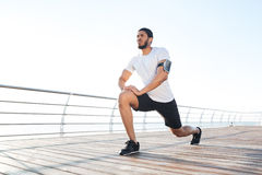 Sportsman stretching legs and listening to music from smartphone. Handsome african young sportsman stretching legs and listening to music from smartphone on pier Royalty Free Stock Images
