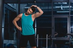 Sportsman stretching neck. In sports hall stock image