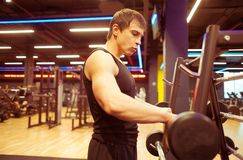 Young fit guy training in gym. Sportsman take barbell near barbell cage in gym Royalty Free Stock Image