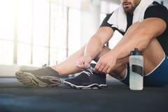 Sportsman ties his sneakers. Sportsman ties his black sneakers Royalty Free Stock Images