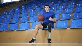 Sportsman tosses a ball while sitting, bionic leg prosthesis. 4K stock video footage