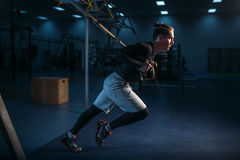 Sportsman on training,endurance workout with ropes. Strong sportsman on training, stretch endurance workout with ropes in gym. Energy exercises in sport club Stock Photos
