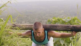 Sportsman training good morning exercise with heavy timber barbell on shoulders outdoor. Fitness man using wooden timber.  stock video footage