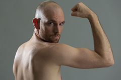 Sportsman training his bicep muscles. Young sportsman showing his bicep muscles Royalty Free Stock Photo
