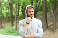 Sportsman training with pedometer gadget. Fitness tracker concept. Man athlete on pensive face with sport fitness gadget. Nature background. Athlete with Stock Images