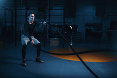 Sportsman on training, workout with battle ropes. In gym. Energy exercises in sport club Stock Photos