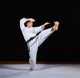 Sportsman trains karate blows against a black background Royalty Free Stock Image