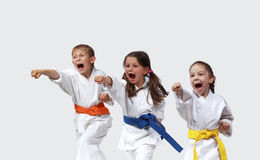 Sportsman and two sportswoman in karategi are beating blows arms Stock Images