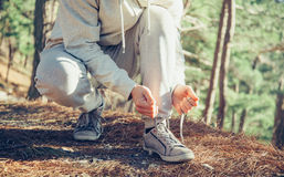 Sportsman tying shoelaces outdoor. Unrecognizable sportsman runner tying shoelaces outdoor near the tree at sunny day Royalty Free Stock Photo