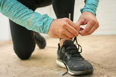 Sportsman tying shoelaces. Young man. Sportsman tying shoelaces. Sportsman tying his shoelaces before the training. Close up Stock Image