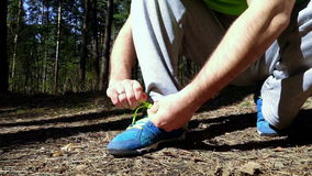 Sportsman tying shoelaces. While standing on his knee stock video footage