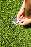 Sportsman tying sports shoes on grass. Urban athlete tying the laces of his sneakers and carrying the movable attached to the arm Royalty Free Stock Photos