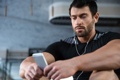 Sportsman using cellphone and listening to music. Sportsman wearing black t-shirt using cellphone and listening to music Royalty Free Stock Photos