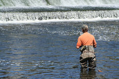 Sportsman in Waders Fishing at Dam. Fisherman in waders downstream from dam. Water rushing over dam visible in background. Horizontal format Stock Images