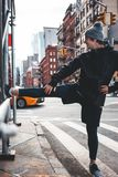 Sportsman warming up and stretching leg in urban streets. Athlete doing exercises and preparing to training run in city stock photo