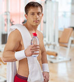 Sportsman wih white cotton towel holding opened bottle of water Royalty Free Stock Photos