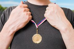 Sportsman (a winner) is putting golden medal on his chest Stock Photo