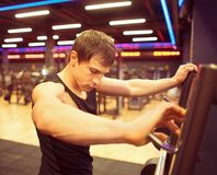 Young fit guy training in gym. Sportsman after workout near barbell cage in gym Stock Photos