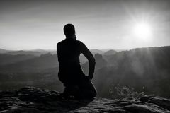 Sportsmann hiker in black sportswear sit on mountain top and take a rest. Tourist  watch down to morning misty valley. Royalty Free Stock Photo